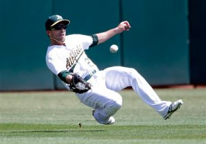 Oakland Athletics center fielder Sam Fuld makes a sliding catch on a pop fly from Seattle Mariners' Dustin Ackley during the first inning of a baseball game on Monday, Sept. 1, 2014, in Oakland, Calif. (AP Photo/Marcio Jose Sanchez)